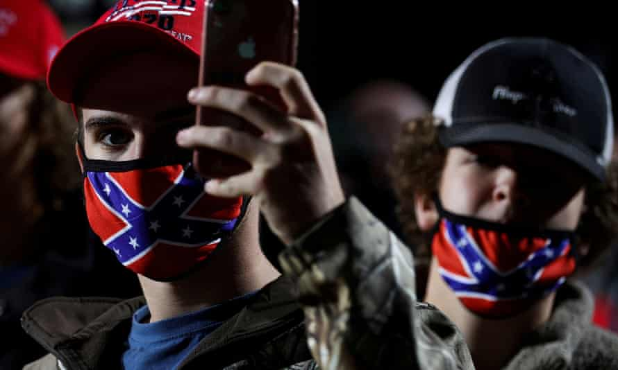 A man wearing a face mask featuring the Confederate battle flag holds a mobile phone during a Trump rally in Georgia.