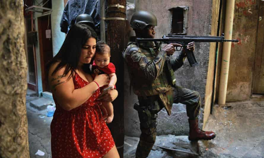 In this file photo taken on 23 September 2017 a woman walks with her baby past a militarized police soldier in the Rocinha favela in Rio de Janeiro, Brazil.