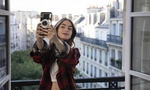 Lily Collins takes a selfie in Emily in Paris.