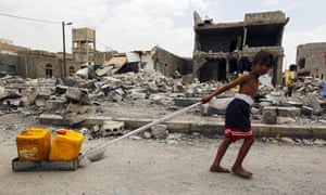 A Yemeni child pulls two jerry cans filled with water past destroyed houses in Sana''a.