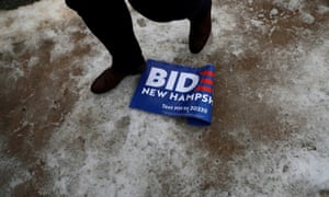A man walks past a sign for Joe Biden lying on the ground on the day of New Hampshire's first-in-the-nation primary in Nashua, New Hampshire.