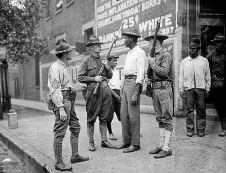 In this 1919 photo provided by the Chicago History Museum, armed National Guard and African American men stand on a sidewalk during race riots in Chicago.
