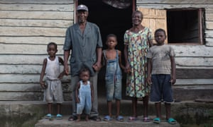 Emmanuel Ngalle stands on the front step of his home with his wife and four grandchildren