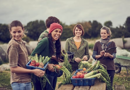 Community farming peers standing together with the allotment produce.