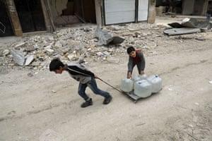 Children pull water bottles along the street in al-Shaar