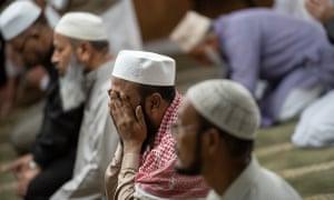 Muslim men pray at the Baitul Mukarram Mosque for Zuhar prayer in Hamtramck, Michigan.