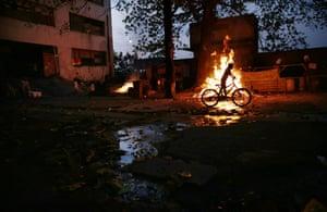 A boy rides a bike past a rubbish fire in the Mangueira favela