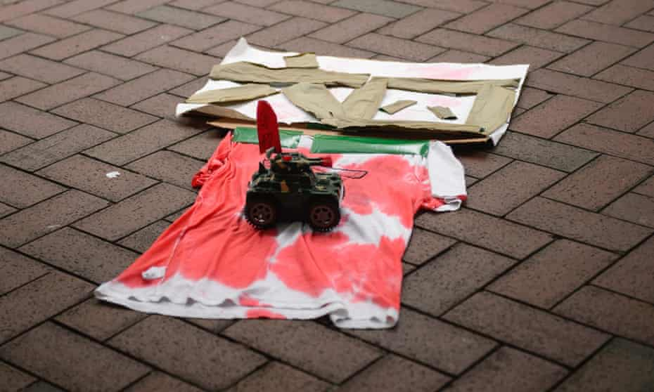 A toy tank rolls over a t-shirt, stained red to mimic blood, and the characters 64 to commemorate the Tiananmen Square crackdown against pro-democracy activists, during a rally in Hong Kong.