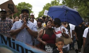 Valerie Castile, center, is kissed by her son's girlfriend, Diamond Reynolds, on Thursday as they march in Minnesota.