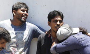 Relatives of people killed in church blasts mourn as they wait outside the mortuary of a hospital in Colombo