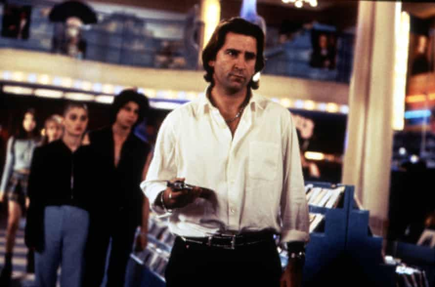 Anthony LaPaglia holding a gun and looking sceptically at someone not in frame