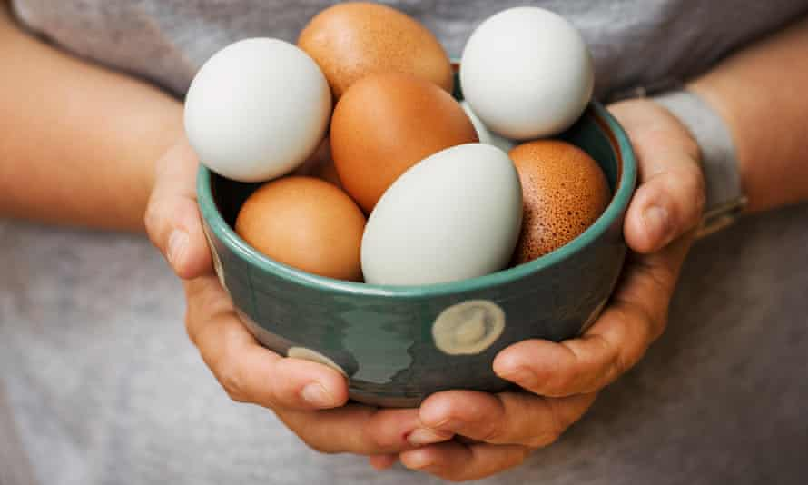 A woman holding bowl with fresh brown and white eggs.