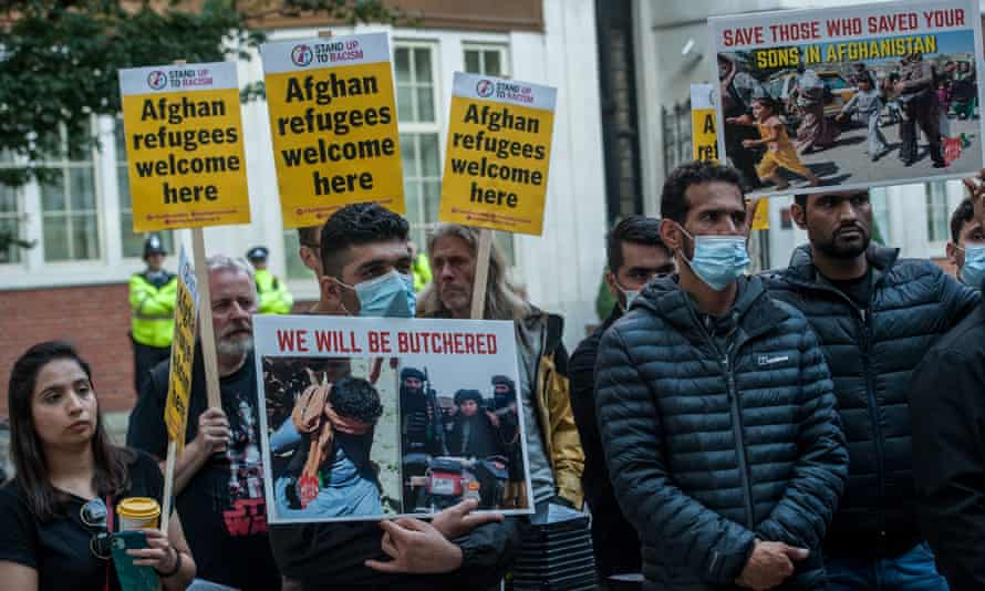 Demonstrators hold placards as Afghans living in London and their supporters attend a protest called by Stand Up To Racism.