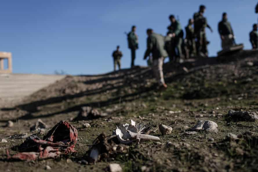 Bones, hair and traditional Yazidi garb at the site of a suspected mass grave near the town of Sinjar, Iraq.