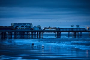 A man walks his dog at dusk in February with the Central Pier in the background