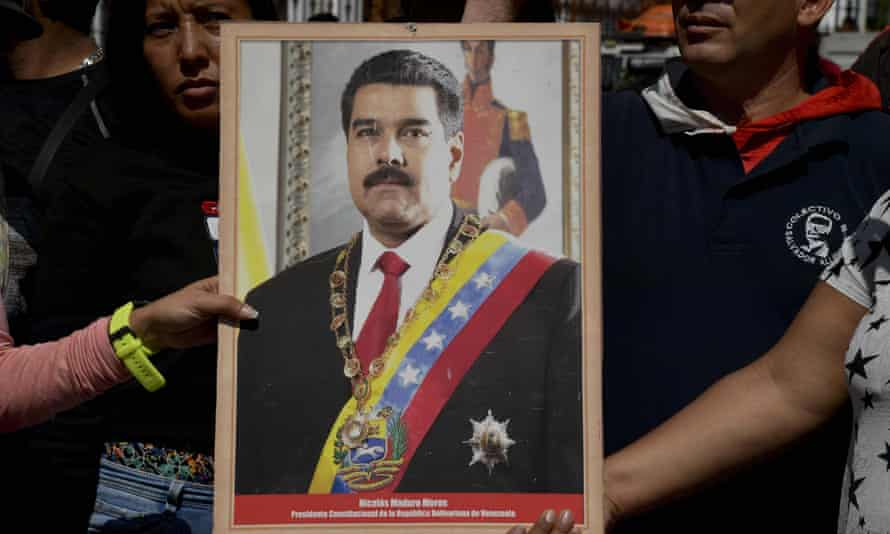 Supporters of Venezuela's President Nicolás Maduro hold a portrait of him during a rally in Caracas on Monday.