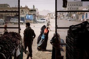 A veiled woman begs outside a grocery store in the village of Azzan, Yemen.