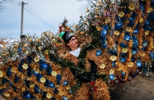 A man in a costume made of hay and reeds and adorned with flowers