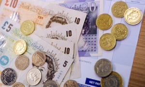 pounds notes and coins and a pay packet