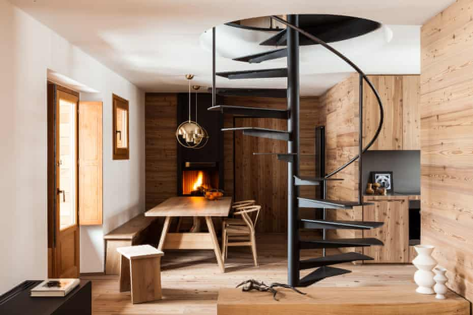 A dining room in a chalet, clad in larch, with a spiral staircase