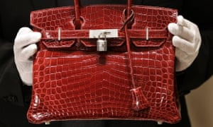 A Hermes employee holds a $129,000 crocodile-skin Birkin bag.