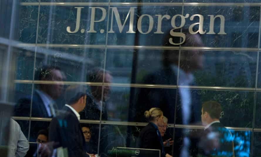 Workers are reflected in the windows of the Canary Wharf offices of JP Morgan in London.