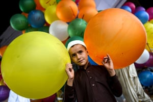 A Pakistani boy holds balloons after offering prayers in Karachi