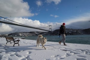 <strong>Istanbul, Turkey</strong><br>A man and his dog enjoy a snowy day by the Bosphorus with Fatih Sultan Mehmet Bridge in the background.