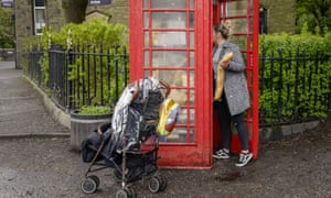 A woman collects food from a disused traditional red phonebox converted into a free community foodbank
