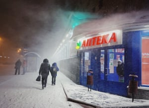 A woman waits for her bus in the warmth of a pharmacy