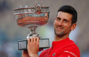 Novak Djokovic celebrates with the trophy after winning the French Open against Stefanos Tsitsipas.