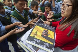 Dharamsala, India A teacher distributes posters to Tibetan school children before a march