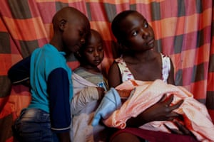 Nairobi, Kenya. Jackline Bosibori, 17, cradles her newborn baby. With schools closed because of the coronavirus pandemic, she is taking care of her six siblings, two of whom are pictured, while her mother is out all day selling vegetables