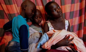 Jackline's younger sisters Maurine Bochaderi, 7, Faith Nyakerario, 5, and Angela Moraa, 12, spend time with Bosibori's newborn daughter at their home in Lindi
