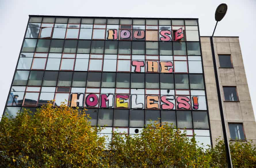 An empty building with a 'House the Homeless' written on the windows.