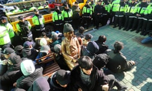 This picture taken on 28 December 2016 in Busan shows South Korean activists staging a sit-in around a statue of a young girl symbolising former 'comfort women' who served as sex slaves for Japanese soldiers during the second world war.