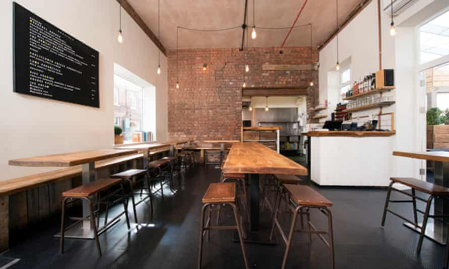 Long tables and benches in the dining room of Burger Shop by a Rule of Tum