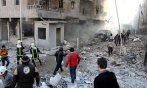 Debris in street, smoke and firefighters after a car bomb in Aleppo, Syria