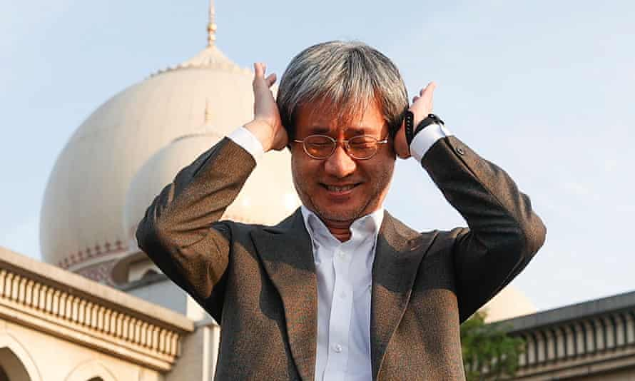 Malaysiakini editor-in-chief Steven Gan gestures outside the palace of justice in Putrajaya on Friday where his site was found guilty of contempt.