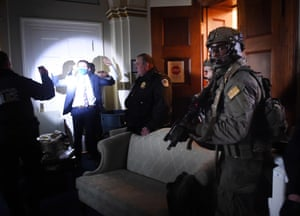 Congress staffers hold up their hands while Capitol Police Swat teams check everyone in the room as they secure the floor of Trump suporters in Washington, DC on January 6, 2021.