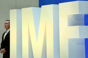 A security personnel stands next to International Monetary Fund logo at IMF headquarters in Washington.