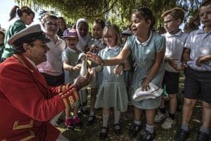The Sovereign's Swan Marker, David Barber, shows a cygnet to schoolchildren from Dedworth Green school