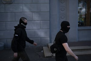 Members of a far right group, some of them wearing balaclavas, march toward a Russian orthodox church in Kiev