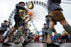 Musicians in a traditional Bavarian costume parade in front of the ferris wheel