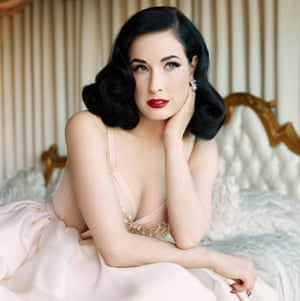 Dita sitting on a bed wearing a white dress