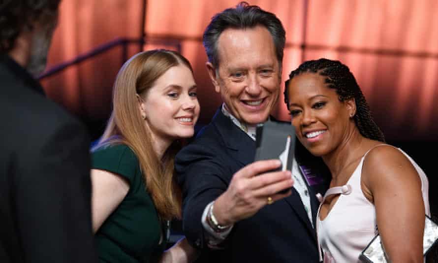 Richard E Grant enjoys a selfie with fellow Oscar nominees Amy Adams and Regina King