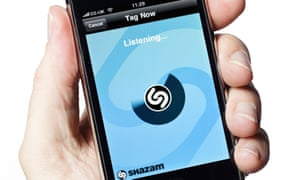 Hand holding mobile phone with Shazam app running