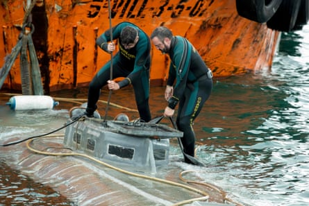 Spanish Civil Guard divers stand over the refloated prow of a submarine used to transport drugs illegally in Aldan, northwestern Spain.