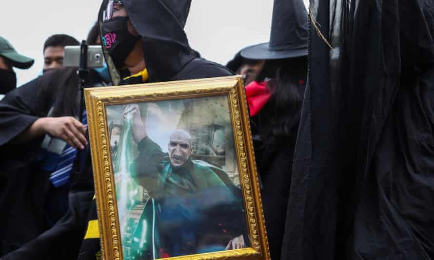 A pro-democracy protester dressed as a wizard holds up a picture of Lord Voldemort.