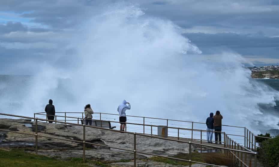 File photo of sightseers dwarfed by spray from large swells at Bondi in Sydney, Australia